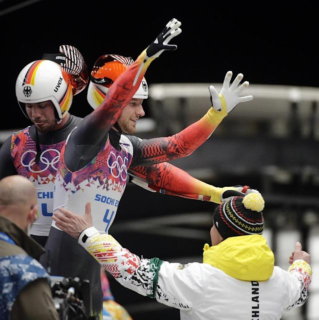 The doubles team of Tobias Wendl and Tobias Arlt from Germany celebrate in the finish area after their final run to win the gold medal during the men's doubles luge at the 2014 Winter Olympics, Wednesday, Feb. 12, 2014, in Krasnaya Polyana, Russia. (AP Photo/Jae C. Hong)