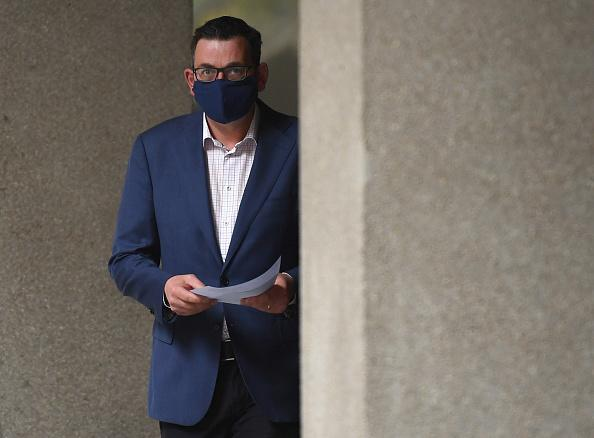 Photo shows Victorian Premier Daniel Andrews entering press conference wearing a face mask in Melbourne.