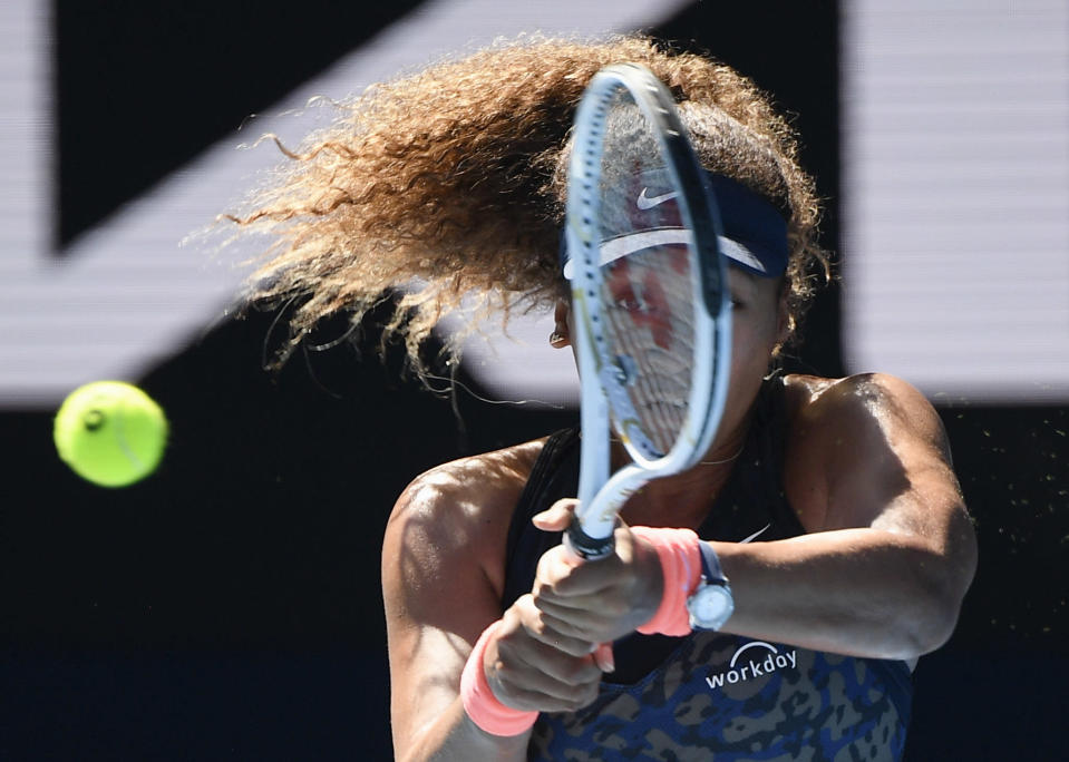 Japan's Naomi Osaka hits a backhand return to United States' Serena Williams during their semifinal match at the Australian Open tennis championship in Melbourne, Australia, Thursday, Feb. 18, 2021.(AP Photo/Andy Brownbill)