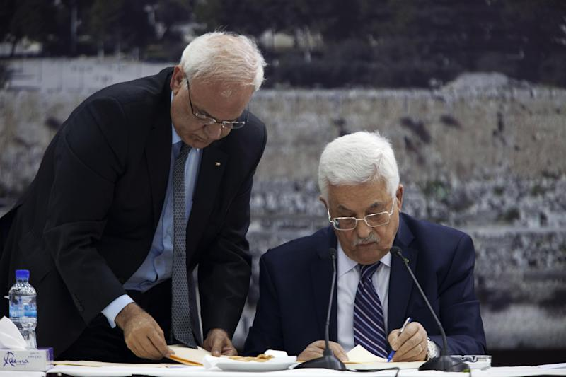 "Palestinian President Mahmoud Abbas, right, jointed by Palestinian chief peace negotiator Saeb Erekat, signs an application to the U.N. agencies in the West Bank city of Ramallah, Tuesday, April 1, 2014. In a dramatic move that could derail eight months of U.S. peace efforts, President Abbas resumed a Palestinian bid for further U.N. recognition despite a promise to suspend such efforts during nine months of negotiations with Israel. Abbas signed ""State of Palestine"" applications for 15 U.N. agencies in a hastily convened ceremony after Israel calls off a promised prisoner release. (AP Photo/Majdi Mohammed)"