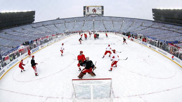 In this photo taken with a fisheye lens, he Detroit Red Wings practice on the outdoor rink for the NHL Winter Classic hockey game against the Toronto Maple Leafs at Michigan Stadium in Ann Arbor, Mich., Tuesday, Dec. 31, 2013. The game is scheduled for New Year's Day. (AP Photo/Paul Sancya)
