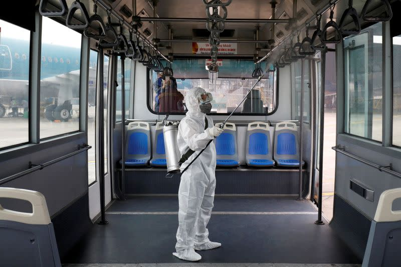 FILE PHOTO: A health worker sprays disinfectant inside a bus to protect from the recent coronavirus outbreak, at Noi Bai airport in Hanoi, Vietnam