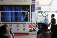 Medical worker gestures inside a COVID-19 vaccination truck in Kuala Lumpur