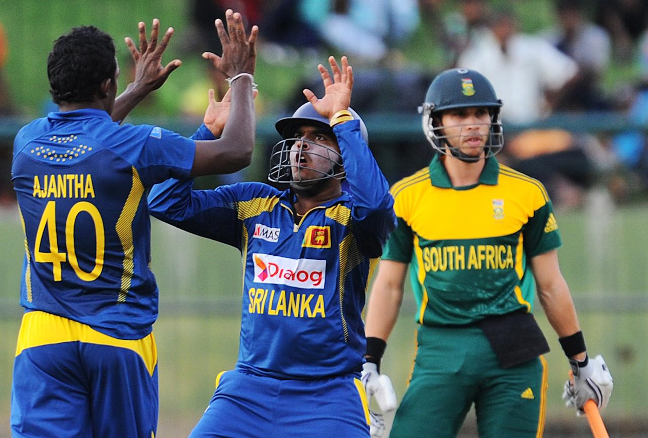Sri Lankan cricketer Ajantha Mendis (L) celebrates the wicket of South African batsman Farhaan Behardien (R) during the third One Day International (ODI) cricket match between Sri Lanka and South Africa at the Pallekele International Cricket Stadium in Pallekele on July 26, 2013. AFP PHOTO/ Ishara S.KODIKARA        (Photo credit should read Ishara S.KODIKARA/AFP/Getty Images)