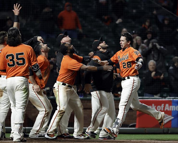 Giants' players, including rookie Christian Arroyo, greet Buster Posey after his game-winning home run against the Reds. (AP)