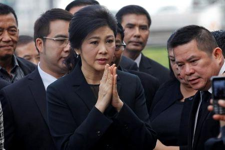 Ousted former Thai Prime Minister Yingluck Shinawatra gestures as she arrives at the Supreme Court for a trial on criminal negligence looking into her role in a debt-ridden rice subsidy scheme during her administration, in Bangkok