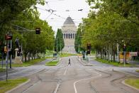 A person crosses an empty street on the first day of a five-day COVID-19 lockdown in Melbourne