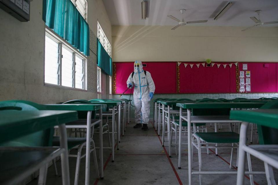 A Fire and Rescue personnel wearing protective gear sprays disinfectant at Sekolah Rendah Agama Kota Damansara 5 January 19, 2021. — Picture by Yusof Mat Isa