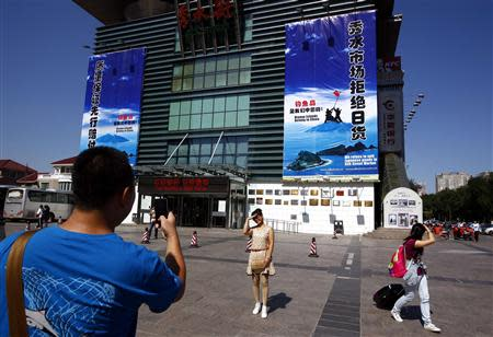 A woman poses for a friend to take a photograph of her standing in front of a large banner adorning the front of Beijing's Silk Street Market, declaring that the famous knock-off designer-wear store refuses 'to sell Japanese goods' due to issues over the disputed East China Sea islands in Beijing in this September 17, 2012 file photo. REUTERS/David Gray/Files