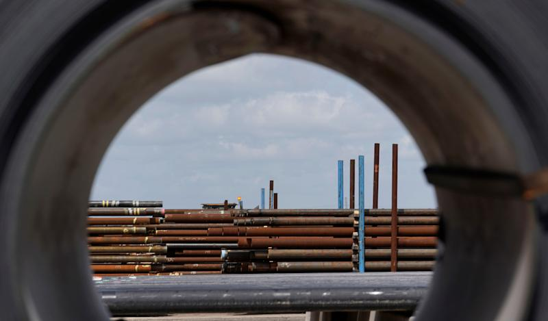 FILE- In this June 5, 2018, file photo steel pipes are seen through a roll of steel at the Borusan Mannesmann Pipe manufacturing facility in Baytown, Texas. Ditching decades of U.S. trade policy that he says swindled America and robbed its workers, President Donald Trump insists he can save U.S. jobs and factories by abandoning or rewriting trade deals, slapping taxes on imports and waging a brutal tariff war with China, America's biggest trading partner. Separately Trump has enraged U.S. allies like Canada and the European Union by declaring their steel and aluminum a threat to America's national security as justification for slapping taxes on them. (AP Photo/David J. Phillip, File)