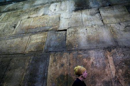 Israel Antiquities Authority archaeologist Tehillah Lieberman stands next to a part of the Western Wall, during a media tour revealing a theatre-like structure which was discovered during excavation works underneath Wilson's Arch, in the Western Wall tunnels in Jerusalem's Old City October 16, 2017. REUTERS/Ronen Zvulun