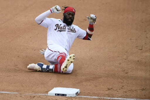 Washington Nationals' Josh Harrison slides into third during the fourth inning of the first baseball game of the team's doubleheader against the Miami Marlins, Saturday, Aug. 22, 2020, in Washington. Harrison singled and went to third on an error. (AP Photo/Nick Wass)