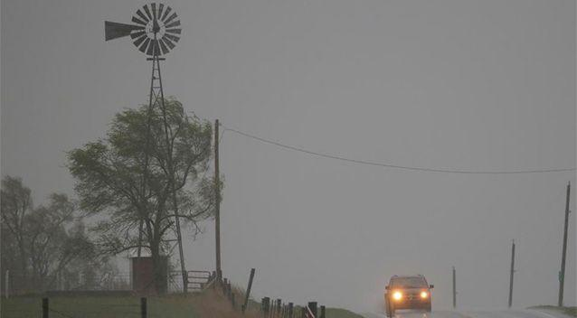 A vehicle tops a hill along U.S. Route 56 as a severe thunderstorm moves through the area near Baldwin City, Kansas. Photo: AP.