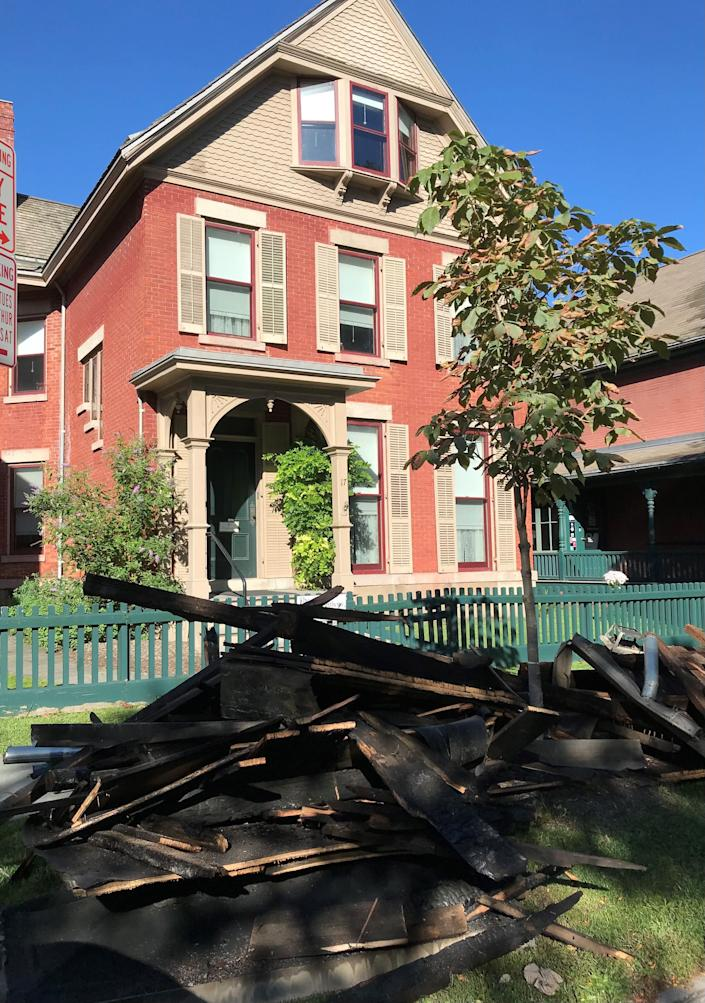 The charred remains of the back porch of the Susan B. Anthony Museum & House on Madison Street are curbside following a fire on Sept. 26, 2021.