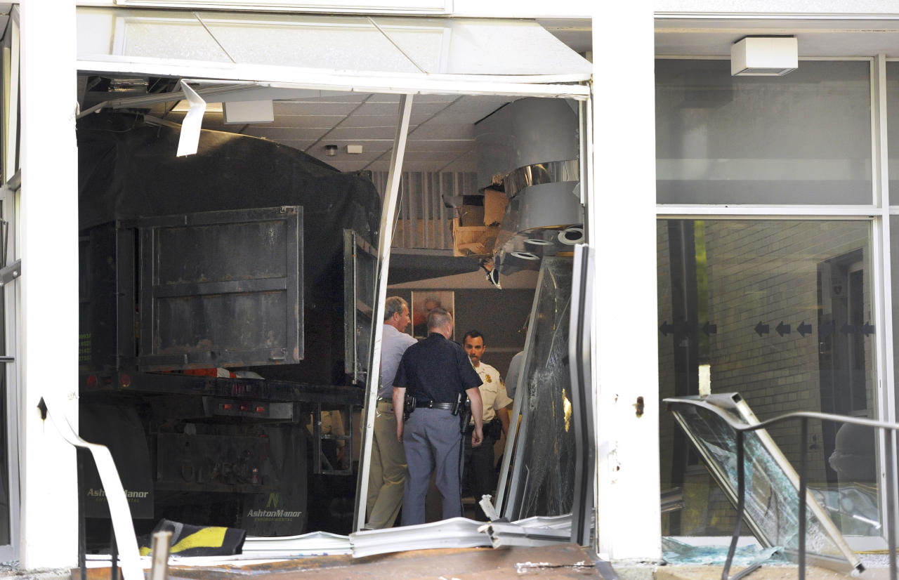 Police and WMAR-TV officials inspect damage caused by a vehicle that crashed into the television station's building Tuesday, May 13, 2014, in Towson, Md. Officials announced that a man was taken into custody after allegedly crashing the vehicle into the building. (AP Photo/Steve Ruark)