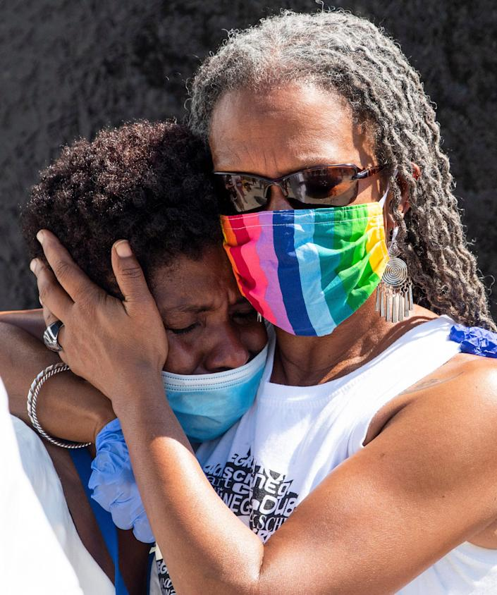 Tafeni English, left, and Lecia Brooks hug during the Juneteenth/Tulsa Riot Vigil held at the Civil Rights Memorial located at the Southern Poverty Law Center in Montgomery, Ala., on Friday June 19, 2020.