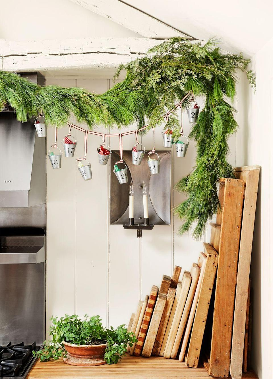 <p>Turn a kitchen garland into an Advent calendar. Attach a ribbon across it and then hang little tin containers labeled with the day of the month and fill them with treats. It'll make the countdown to Christmas even more exciting. </p>