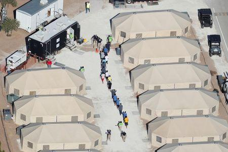 "Immigrant children now housed in a tent encampment under the new ""zero tolerance"" policy by the Trump administration are shown walking in single file at the facility near the Mexican border in Tornillo, Texas"