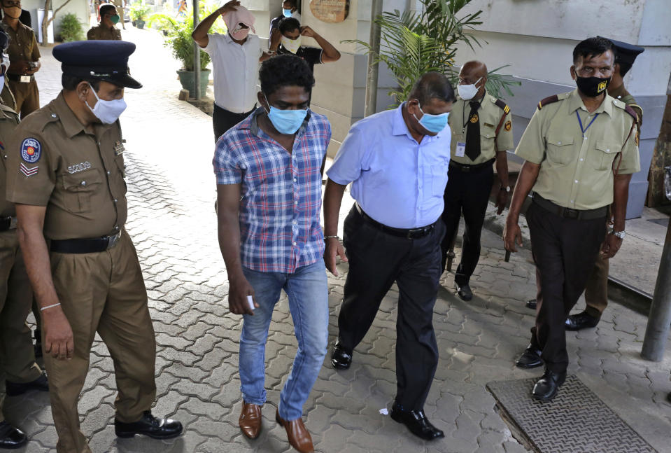 Sri Lankan police officials escort arrested narcotics unit police officers who are accused smuggling at a magistrate court in Colombo, Sri Lanka, on July 2, 2020. For years, authorities in Sri Lanka have tried to rid the Indian Ocean island nation of illegal drugs. But a drug ring allegedly including more than a dozen officers from a key national narcotics unit has exposed how much of a challenge that goal brings. (AP Photo)