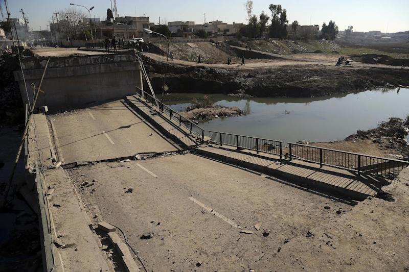 People inspect a bridge destroyed by Islamic State militants in a neighborhood recently liberated from Islamic State on the eastern side of Mosul, Iraq, Thursday, Jan. 12, 2017. Small stalls and carts have sprung up outside the bombed-out restaurants and cafes in eastern Mosul, selling fresh vegetables, cigarettes and cellphones to the thousands of civilians still living in neighborhoods where the Iraqi military has driven out the extremists of the Islamic State group.(AP Photo/ Khalid Mohammed)