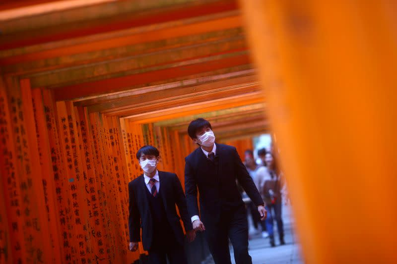 FILE PHOTO: Visitors, wearing protective masks following an outbreak of the coronavirus disease (COVID-19), walk through wooden torii gates at Fushimi Inari Taisha shinto shrine in Kyoto