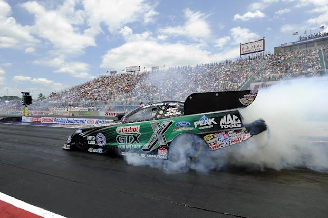 In this photo provided by the NHRA, Funny Car icon John Force performs a burnout in his Castrol GTX High Mileage Ford Mustang Sunday, July 6, 2014, at the Summit Racing Equipment NHRA Nationals at Norwalk, Ohio. Force outran longtime rival Ron Capps to earn his 140th career victory and second win of the NHRA Mello Yello Drag Racing Series season. (AP Photo/NHRA, Marc Gewertz)