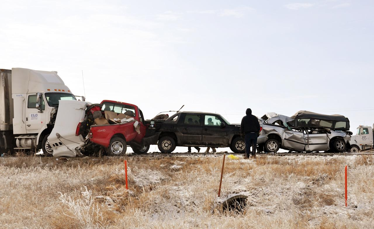 Crushed vehicles and semi-trailers sit on Highway 20, Monday, March 5, 2012, after chain-reaction collisions occurred involving nearly two-dozen vehicles near Webster City, Iowa. Authorities are blaming the pileups on poor visibility due to fog and thick, black smoke billowing from burning hay bales nearby. Eight people were hospitalized, two are reportedly in serious condition. (AP Photo/The Messenger, Jessie Helling)