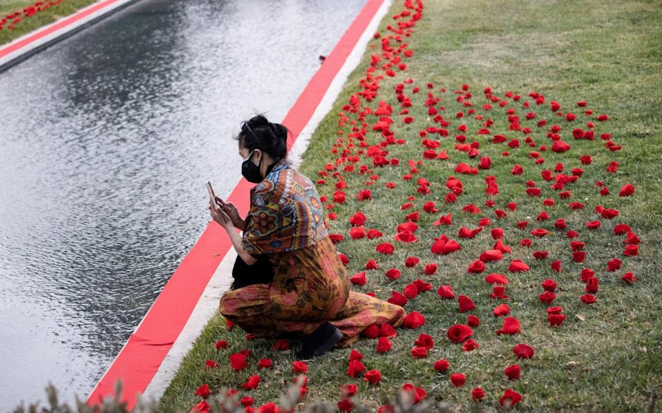 A person uses her mobile phone by a tribute to the victims of the COVID-19 pandemic by the Reflecting Pool at the Hollywood Forever Cemetery - Mario Anzuoni/Reuters
