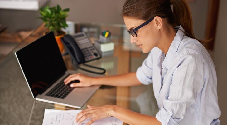 A business owner uses tax software to get their finances in order before it's time to file.