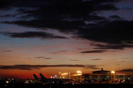 Planes sit at the terminal as the sun sets at Ninoy-Aquino International Airport in Manila, Philippines