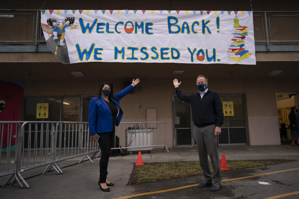 Los Angeles Unified School District Superintendent Austin Beutner, right, and Gabriela Rodriguez, principal of Heliotrope Avenue Elementary School, pose for photos on the first day of in-person learning in Maywood, Calif., Tuesday, April 13, 2021. More than a year after the pandemic forced all of California's schools to close classroom doors, some of the state's largest school districts are slowly beginning to reopen this week for in-person instruction. (AP Photo/Jae C. Hong)