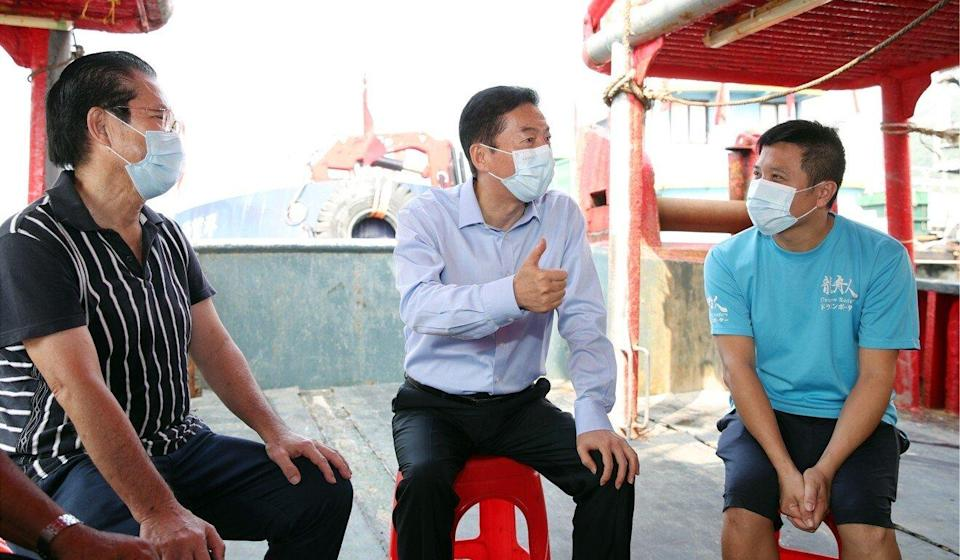 Luo Huining (centre) chats with fishermen in Aberdeen. Photo: Liaison office website