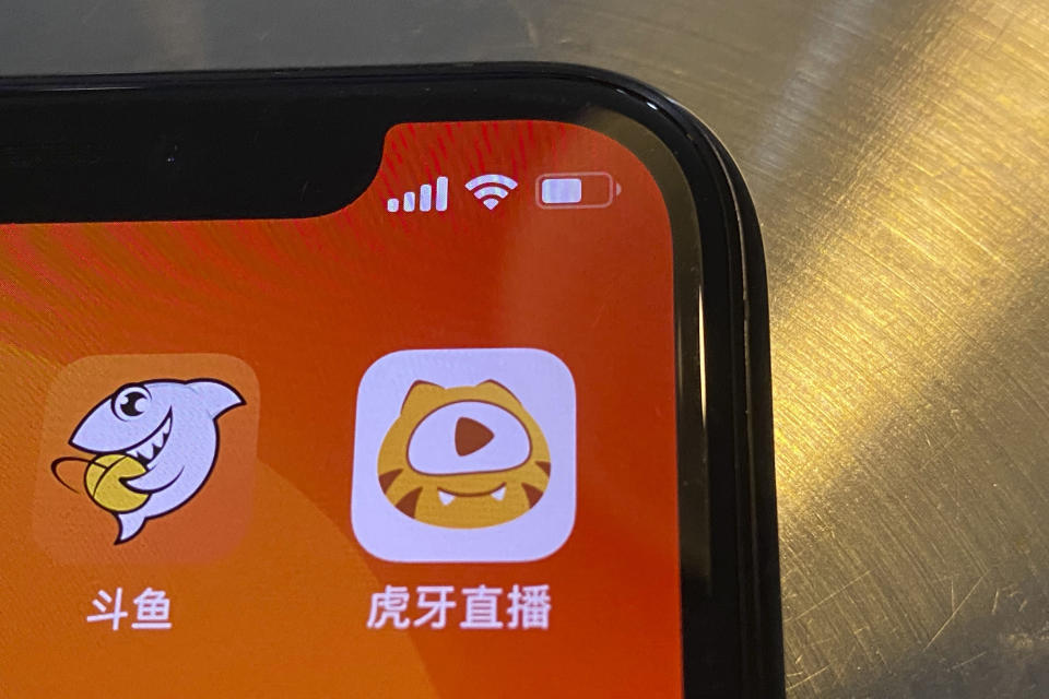 The apps Douyu at left and Huya at right are seen on a screen in Beijing on Saturday, July 10, 2021. China's market regulator on Saturday blocked the merger of Tencent-backed game streaming platforms Douyu and Huya following an anti-monopoly investigation, as authorities ramp up scrutiny of some of the country's biggest technology companies. (AP Photo/Ng Han Guan)
