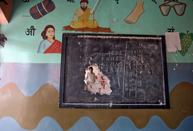 A man is seen through a hole on a classroom wall after the school building was attacked by a mob in a riot affected area following clashes between people demonstrating for and against a new citizenship law in New Delhi