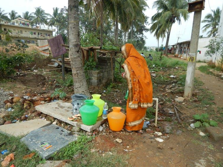"""<span class=""""caption"""">A woman collects drinking water from a well in Bangalore, India.</span> <span class=""""attribution""""><span class=""""source"""">Prathigna Poonacha</span>, <span class=""""license"""">Author provided</span></span>"""