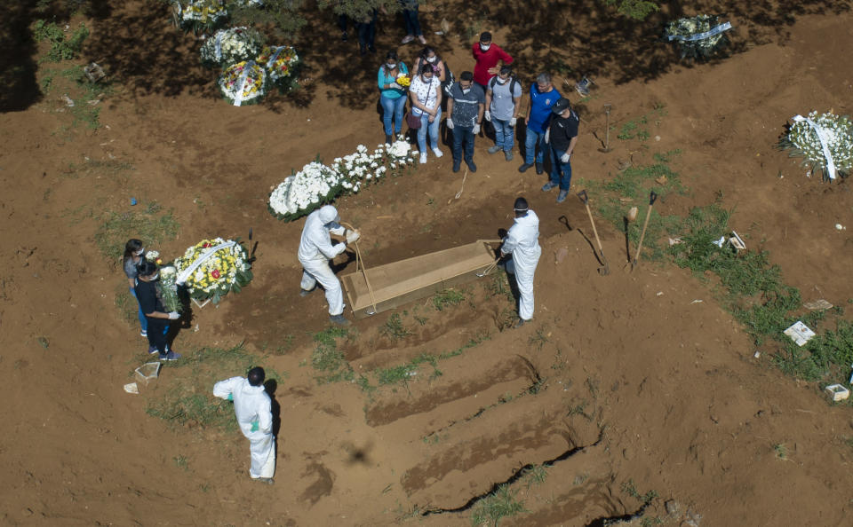Cemetery workers bury a person at the Vila Formosa cemetery in Sao Paulo, Brazil, Wednesday, April 1, 2020. Vila Formosa cemetery, the largest in Latin America, has had a 30 percent increase in the number of burials after the start of the spread of the new coronavirus, according to the cemetery's administration. (AP Photo/Andre Penner)