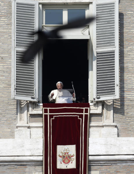 A pigeon flies in front of Pope Benedict XVI as he waves to the faithful during the Angelus noon prayer he celebrated from the window of his studio overlooking St. Peter's square, at the Vatican, Sunday, Feb. 17, 2013. Pope Benedict XVI blessed the faithful from his window overlooking St. Peter's Square for the first time since announcing his resignation, cheered by an emotional crowd of tens of thousands of well-wishers from around the world. (AP Photo/Alessandra Tarantino)