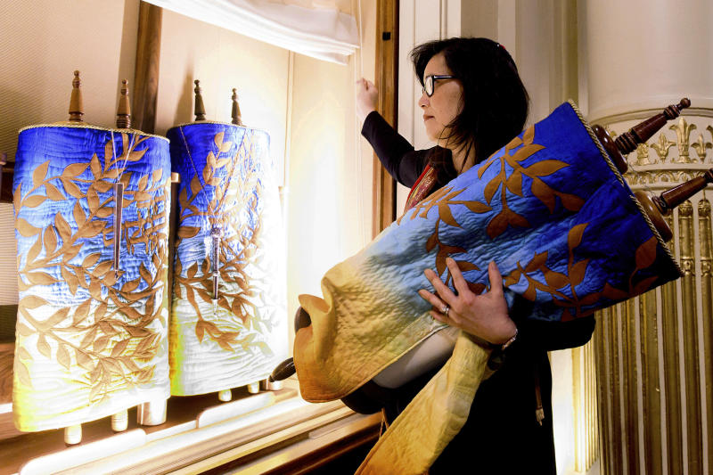 """In this Saturday, Feb. 1, 2020, photo, Rabbi Jacqueline Mates-Muchin removes a Torah scroll from the ark, a cabinet that houses scrolls of the Hebrew Bible, while preparing for Shabbat morning service at Temple Sinai in Oakland, Calif. In September 2017, on the first day of Rosh Hoshana, the Jewish new year, a security guard found an anti-Semitic message scrawled on an outdoor wall of Temple Sinai. """"Since 2017, the congregation has been looking to try to feel safe,"""" she said. """"It's another layer that we always have to be conscious of."""" (AP Photo/Noah Berger)"""
