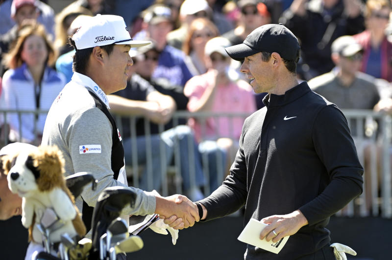 Sungjae Im, left, of South Korea, and Rory McIlroy, of Northern Ireland, shake hands before hitting their tee shots on the first hole during the third round of the Arnold Palmer Invitational golf tournament, Saturday, March 7, 2020, in Orlando, Fla. (AP Photo/Phelan M. Ebenhack)