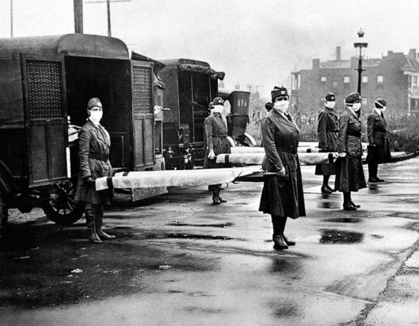 PHOTO: The St Louis Red Cross Motor Corps on duty with mask-wearing women holding stretchers at the backs of ambulances during the Influenza epidemic, St Louis, October, 1918. (Underwood Archives/Getty Images)