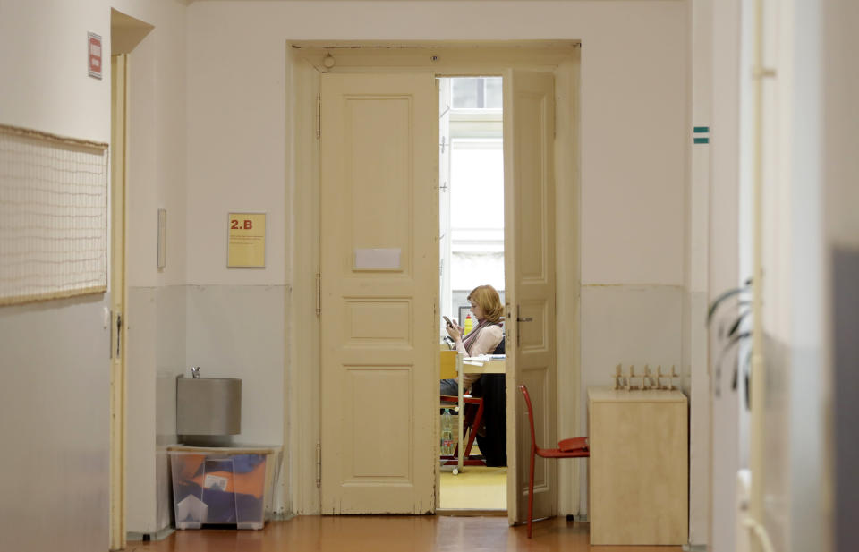 A teacher sits in an empty classroom at a closed school in Prague, Czech Republic, Wednesday, Oct. 14, 2020. Amid widespread efforts to curb the new wave of coronavirus infections in one of the hardest hit European countries, the Czech Republic closed again all its schools on Wednesday. (AP Photo/Petr David Josek)