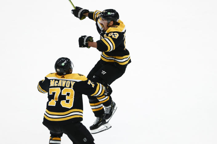 Boston Bruins' Brad Marchand jumps while celebrating his tying goal with teammate Charlie McAvoy in the third period of Game 2 during an NHL hockey second-round playoff series against the New York Islanders, Monday, May 31, 2021, in Boston. (AP Photo/Winslow Townson)