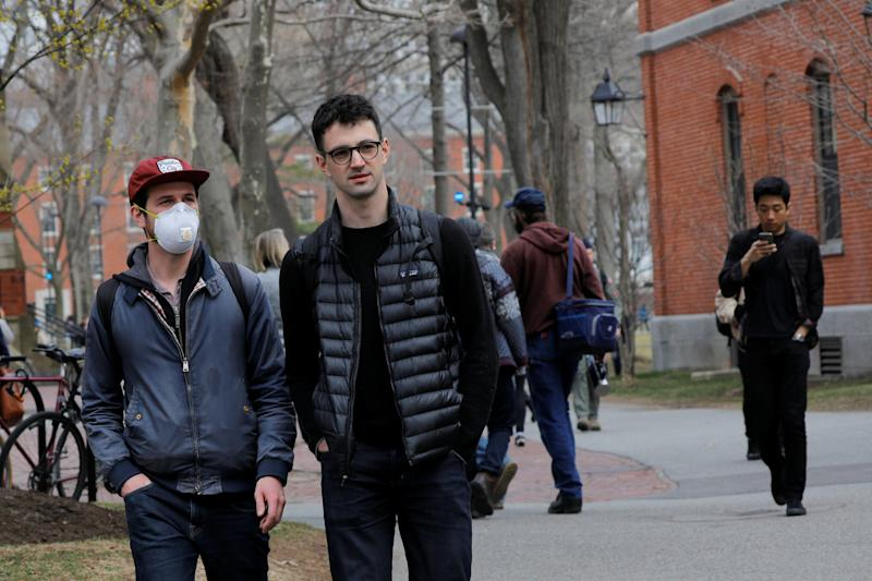 A student wearing a mask, because his cancer treatment has left him immunosuppressed and vulnerable to diseases such as the coronavirus, walks through the Yard at Harvard University, after the school asked its students not to return to campus after Spring Break and said it would move to virtual instruction for graduate and undergraduate classes, in Cambridge, Massachusetts, U.S., March 10, 2020. REUTERS/Brian Snyder