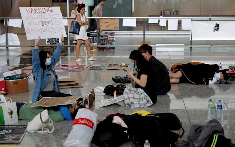 A protester shows a placard to travellers as they continue their sit-in rally at the airport in Hong Kong on Wednesday - AP