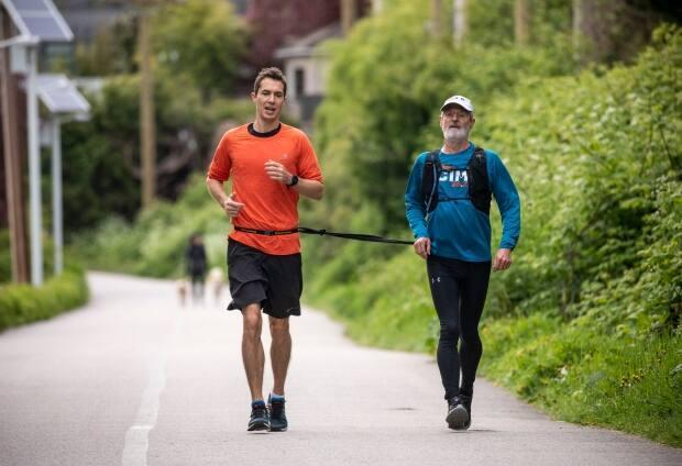 Peter Field, right, who is blind, runs with his guide Sam O'Shea using a tether in Vancouver this week. On Saturday, Field put his training to use, completing the Vancouver Marathon in four hours and 23 minutes. (Ben Nelms/CBC - image credit)
