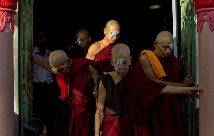 """In this Oct. 23, 2013 photo, Buddhist monks with eye patches exit a room in a Buddhist shrine following simple operations to remove cataracts in Bago, Myanmar. Five decades of isolation, military rule and woeful health care have left Myanmar with one of the highest rates of blindness in the region. Now the veil of darkness is starting to lift, thanks to an """"assembly line"""" surgical procedure that allows cataracts to be removed safely, without stitches, through two small incisions. (AP Photo/Gemunu Amarasinghe)"""