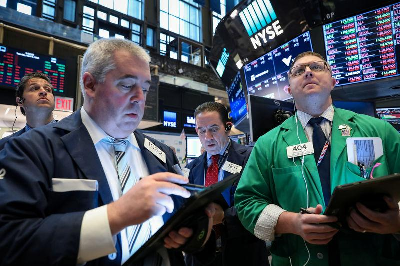 FILE PHOTO: Traders work on the floor at the New York Stock Exchange (NYSE) in New York, U.S., April 9, 2019. REUTERS/Brendan McDermid