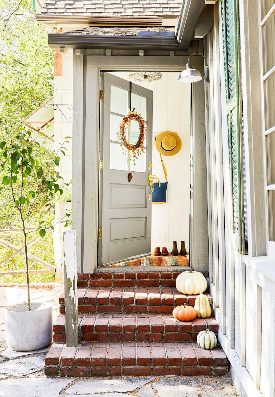 """<p>Out of the four <a href=""""https://www.housebeautiful.com/room-decorating/colors/tips/g912/fall-color-schemes/"""" rel=""""nofollow noopener"""" target=""""_blank"""" data-ylk=""""slk:seasons"""" class=""""link rapid-noclick-resp"""">seasons</a>, your front door probably gets the most foot traffic during <a href=""""https://www.housebeautiful.com/home-remodeling/interior-designers/tips/g956/cozy-fall-home-decor/"""" rel=""""nofollow noopener"""" target=""""_blank"""" data-ylk=""""slk:fall"""" class=""""link rapid-noclick-resp"""">fall</a>. From trick-or-treaters to <a href=""""https://www.housebeautiful.com/entertaining/table-decor/g1535/fall-table-decorating-ideas/"""" rel=""""nofollow noopener"""" target=""""_blank"""" data-ylk=""""slk:Thanksgiving"""" class=""""link rapid-noclick-resp"""">Thanksgiving</a> guests—and, hopefully, deliveries with gifts for the upcoming <a href=""""https://www.housebeautiful.com/entertaining/holidays-celebrations/tips/g2804/outdoor-christmas-decorations/"""" rel=""""nofollow noopener"""" target=""""_blank"""" data-ylk=""""slk:holidays"""" class=""""link rapid-noclick-resp"""">holidays</a>—there will be plenty of eyes on your front door, which means it's time to spruce things up with stylish fall door decor. If you're inclined to break out your go-to <a href=""""https://www.housebeautiful.com/home-remodeling/diy-projects/g2586/fall-wreaths/"""" rel=""""nofollow noopener"""" target=""""_blank"""" data-ylk=""""slk:fall wreath"""" class=""""link rapid-noclick-resp"""">fall wreath</a> and call it a day, hold off until you see these fun, festive, and elevated wall decor ideas. Read on for 25 chic ways to dress up your front door for the fall <span class=""""redactor-unlink"""">season ahead</span> (String lights! Seasonal door swag!). </p>"""