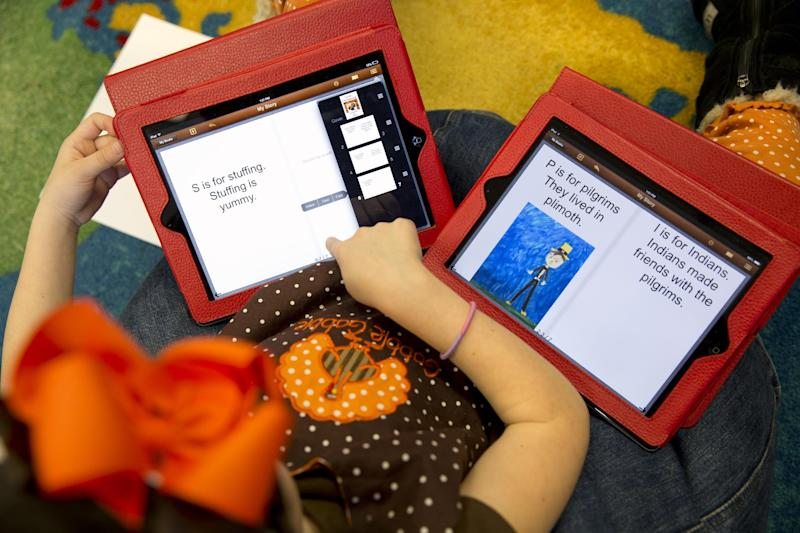 This photo taken Nov. 25, 2013 shows Isabelle Fontana, 7, working on two iPads for an e-book about Thanksgiving in her second grade classroom at Jamestown Elementary School in Arlington, Va. Isabelle was working on the text as a classmate made drawings to be photographed and inserted in the e-book. Needed to keep a school building running these days: Water, electricity _ and broadband. Interactive digital learning on laptops and tablets is, in many cases, replacing traditional textbooks. Students are taking computer-based tests instead of fill-in-the bubble exams. Teachers are accessing far-off resources for lessons. (AP Photo/Jacquelyn Martin)