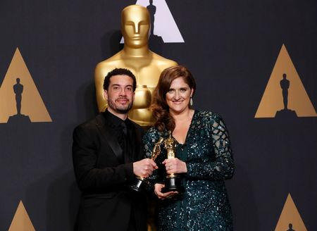 FILE PHOTO - Ezra Edelman and Caroline Waterlow hold their Best Feature Documentary Oscars for O.J: Made in America, at the 89th Academy Awards, Hollywood